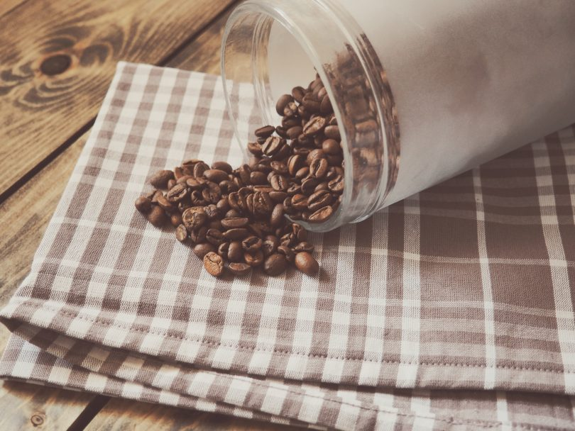 Coffe Beans in glass jar spilling out onto dishcloth