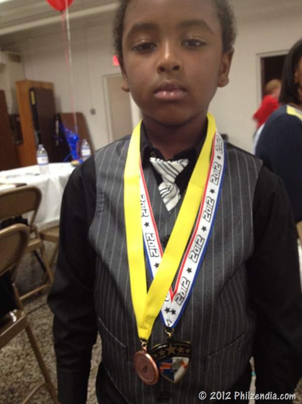 Z.E.N. showing off his medals for winning track relays